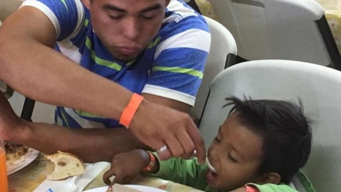 Man feeding boy